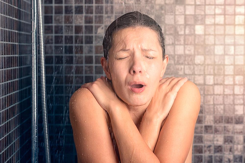 シャワーの途中で水が出て驚く女性